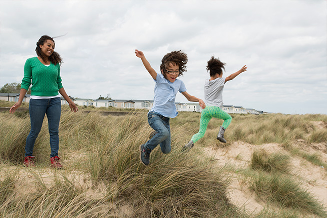 kids jumping in sand dunes
